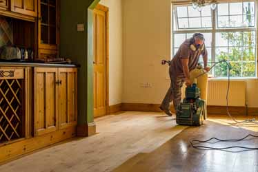 Floor Sanding in progress - Image of work man carrying out wood floor sanding in kitchen