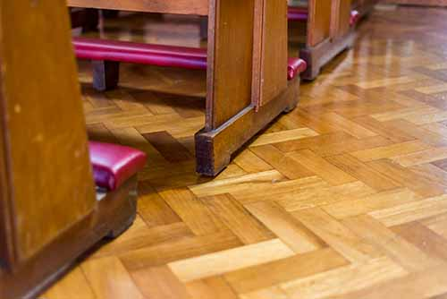 Specialist wood flooring product - Image of Church pews on Parquet Wood Floor in Herringbone pattern fitted in Church