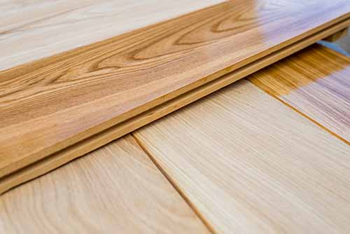 Oak wood floor boards showing contrast between raw and finished wood flooring product