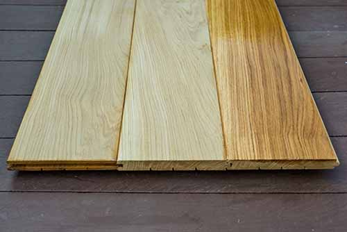 Oak wood floor boards showing contrast between raw and varnished wood flooring products