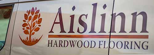 Side view of Aislinn Hardwood Flooring van bearing company name and logo